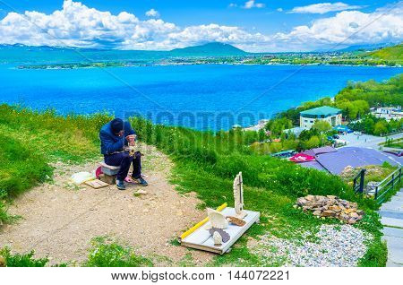 SEVAN ARMENIA - MAY 31 2016: The local sculptor at work on the hill of Sevan Peninsula with the bright blue lake on the background on May 31 in Sevan