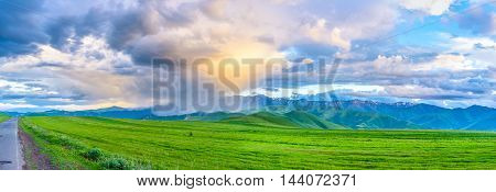 The sunset light reflects in the rainy cloud that gets bright golden color Syunik Province Armenia.