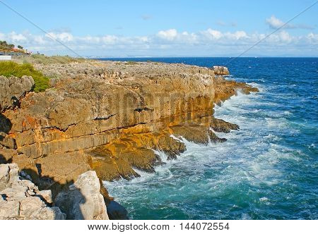 The winding rocky coast of Atlantic Ocean is the best place for the daily walk enjoying the nature's beauty in Cascais resort Portugal.
