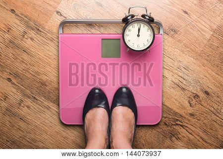 the feet of a woman standing on bathroom scales to turn