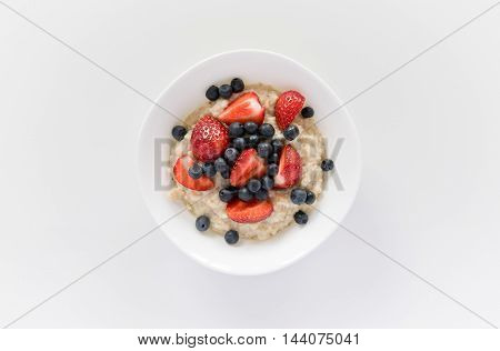 Healthy breakfast with summer berries. Morning oatmeal porridge with fresh strawberries and blueberries.