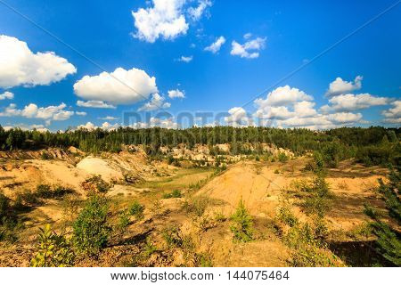 Quarry Or Lake Or Pond With Sandy Beach, Brown Dirty Water, Trees And Hills