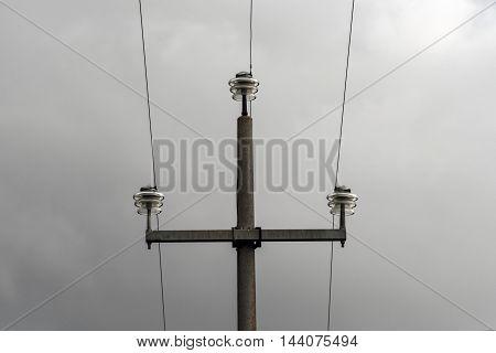 electricity pole head grey cloudy sky background closeup