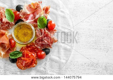 Plate with tasty meat snack on wooden table