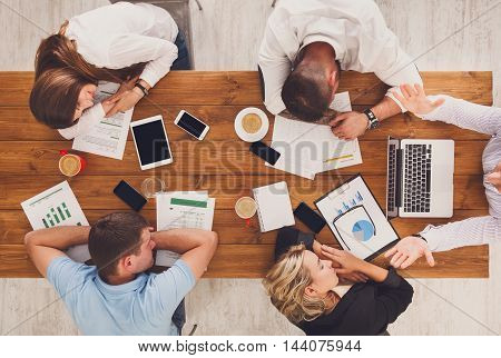 Group of business people exhausted sleep in office, top view of wooden table with mobile phones, laptop, tablet and papers with diagram. Men and women team tired and relaxed after brainstorm