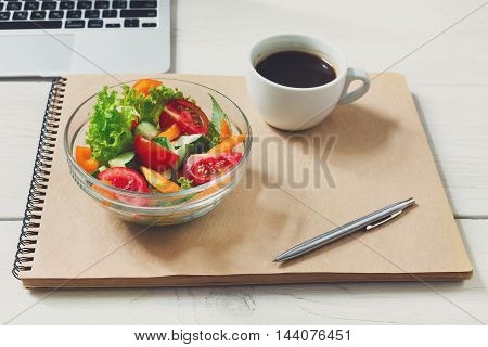 Healthy business lunch in office, vegetable salad bowl on white wooden desk and notepad with pen. Salad bowl and americano coffee cup. Snack at break time