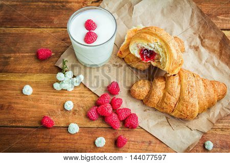 Cornetto with raspberry jam filling, glass of milk or yoghurt, fresh ripe berries and white flowers on the table, served for breakfast or snack