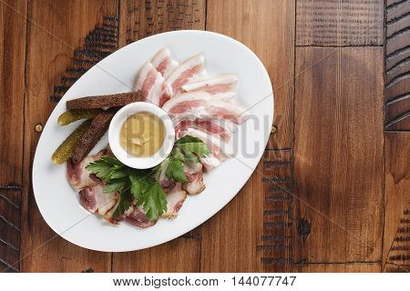 smoked and salted lard on a plate. bacon with sauce and greens.