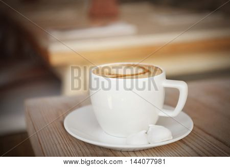 Cup of coffee with meringues on wooden table