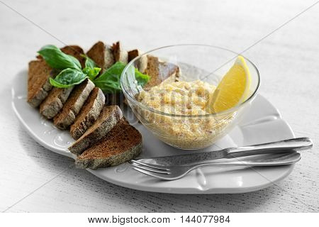 Plate with bread and caviar on wooden table