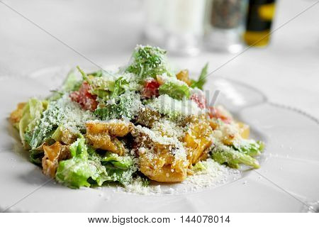 Tasty salad on white wooden table in cafe