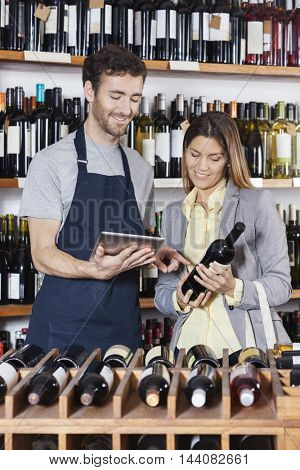 Smiling Salesman Showing Wine Information To Customer On Digital