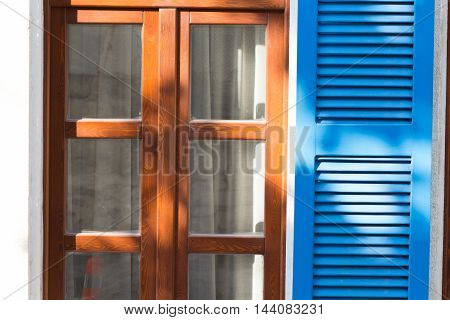 wooden window with blue shutters in a traditional Mediterranean style