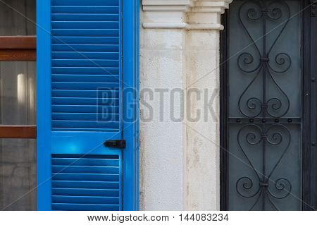 Traditional vintage facade with blue shutters and metal bars