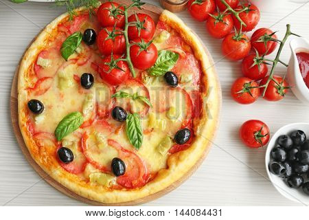 Delicious pizza on wooden cutting board