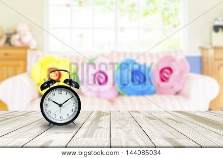 Alarm Clock On Wood Table And Blurry Interior Living Room In Background.