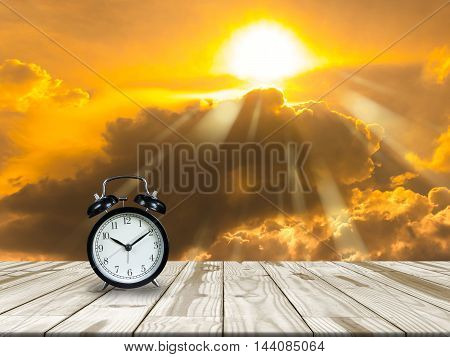 Alarm Clock On Wood Table And Golden Sky.