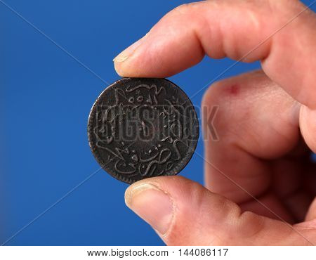 picture of a Fingers hold old coin from Ottoman empire