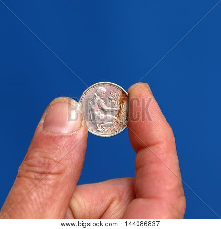 picture of a Fingers hold old coin from Austria