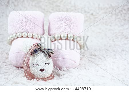 Pink booties for babies with several bracelets and one brooch on the white fur