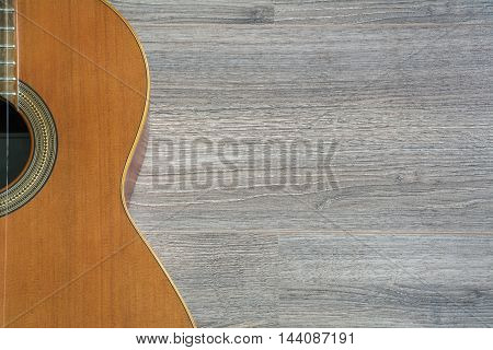 Yellow guitar on the brown wooden background