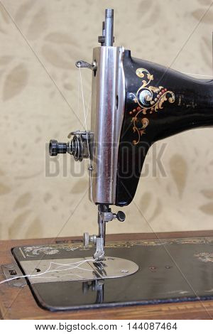 Vintage hand sewing machine in black on wooden stand