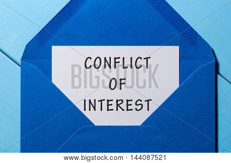 Conflict of interest text written in letter at blue envelope.