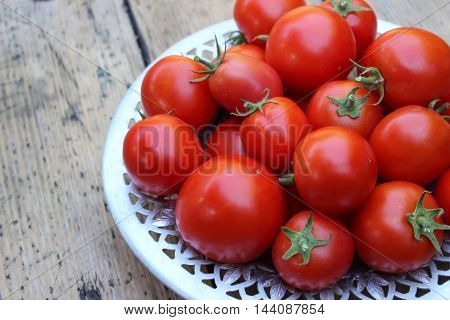 Red tomatoes on plate on background of boards