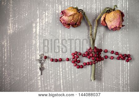 Catholic rosary and faded roses on grey wooden background