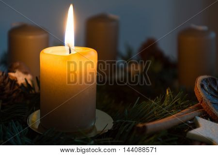 first candle on decorative advent wreath is burning in a dark environment