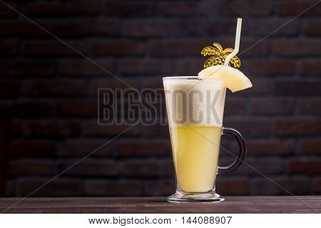 Alcoholic Cocktail Standing On A Wooden Table . With A Straw , Palm And Orange .