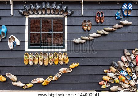 Traditional dutch shoes called clogs on a wooden house as decoration