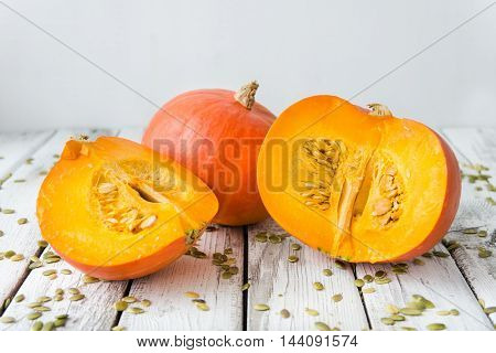 fresh orange pumpkin with seeds on a white wood background rustic style selective focus