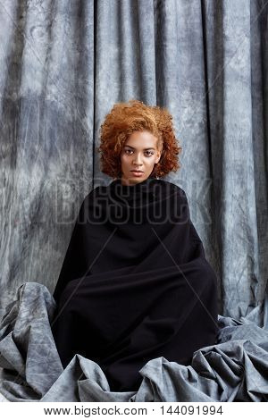 Young beautiful african girl looking at camera, posing, wrapping up  in grey cloth. Copy space.