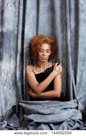 Young beautiful african girl posing with closed eyes, wrapping up  in grey cloth. Copy space.