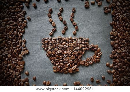Cup from coffee beans with smoke on grey stone surface texture and wooden table with scattered seeds frame. Cafe hot drink background. Soft color toning, top view