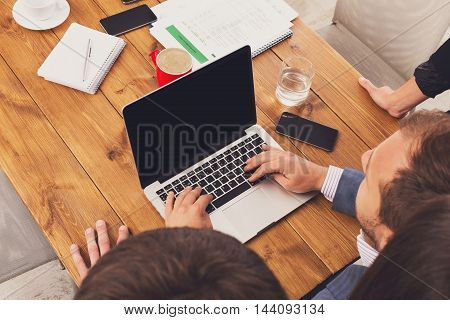 Business people looking at laptop screen in the office, unrecognizable above view. Successful corporate team of female and male coworkers check internet site of company, partners and colleagues.
