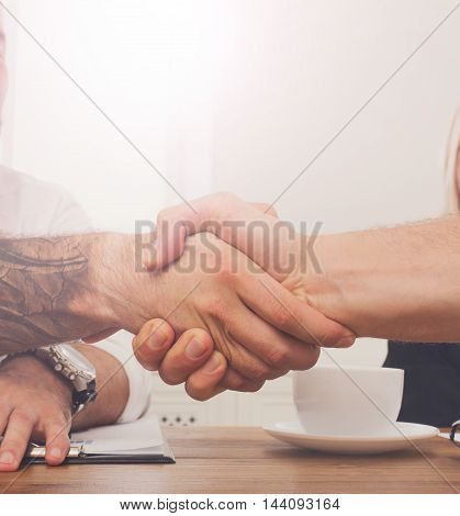 Business handshake at office corporate meeting, contract conclusion and successful agreement concept. Modern hipster businessman and other man's hands meet at window background.