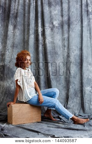Young beautiful african girl sitting at wooden box, smiling over grey cloth background. Copy space.