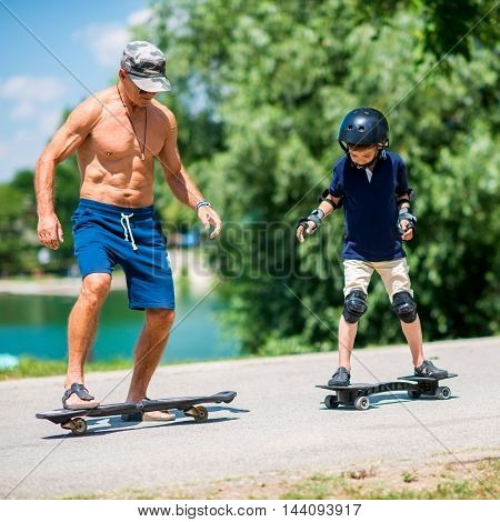 Senior Man And Little Boy Riding Snakeboards