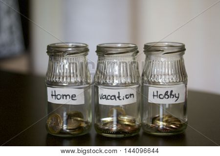 Three jars - piggy bank. In the miscellaneous expenses. They are glued to the tape to write her goal of spending. At the bottom poured a bit of coins. Budget Management.
