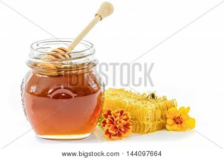 Jar full of honey next to the honeycomb and bee and flowers on white background