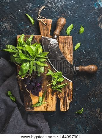 Fresh green and purple basil leaves with herb chopper knife on rustic cutting board over grunge dark blue plywood texture. Top view, vertical composition