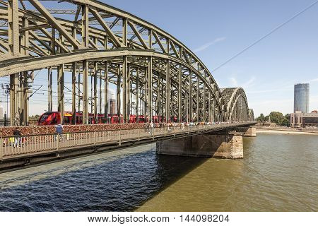 COLOGNE GERMANY - AUG 7 2016: Red Deutsche Bahn train at the Hohenzollern Bridge in Cologne North Rhine-Westphalia Germany