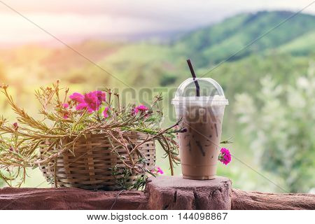 Closeup ice coffee in plastic cup with beautiful flower on  mountain background.