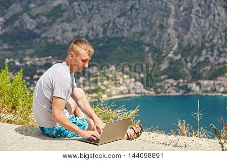 Young freelancer using laptop sitting near the sea.Happy smiling man working online.Studying and learning using notebook computer.Freelance workbusiness people concept.