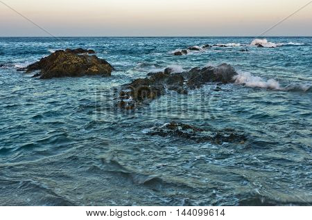 Waves and dangerous sea rocks at sunset, south coast of Sithonia, Chalkidiki, Greece