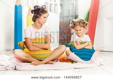 Little girl with her mother had an argument and sittig sulkily