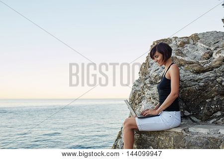 Beautiful Young Freelancer Woman Using Laptop Sitting Near The Sea.happy Smiling Girl Working Online