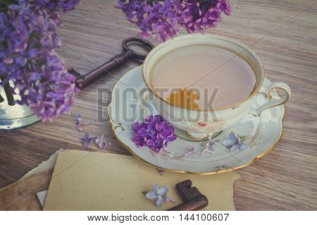 summer cup of tea with lilac and vintage photos, retro toned